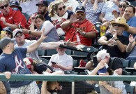 Baseball fan blocks bat from hitting kid